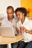 Couples dinant à l'extérieur utilisant un ordinateur portatif Photos libres de droits