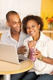 Couples dinant à l'extérieur utilisant un ordinateur portatif Photographie stock