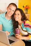 Couples dinant à l'extérieur utilisant un ordinateur portatif Images stock