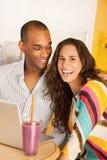 Couples dinant à l'extérieur utilisant un ordinateur portatif Image libre de droits