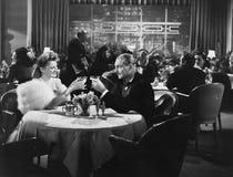 Couples dinant dans le restaurant serré (toutes les personnes représentées ne sont pas plus long vivantes et aucun domaine n'exis Image stock
