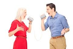 Couples discutant par un téléphone de boîte en fer blanc Photos libres de droits