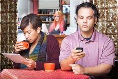 Couples distraits utilisant des dispositifs Image stock
