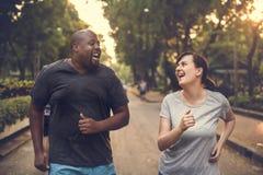 Couples divers fonctionnant au parc photo stock