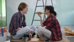Couples diy mignons partageant la pizza pendant la restauration à la maison banque de vidéos
