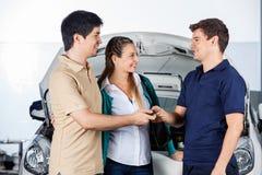 Couples donnant des clés de voiture au mécanicien Photographie stock libre de droits