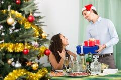 Couples donnant des présents au dîner de Noël Images libres de droits