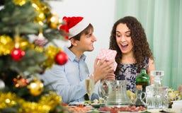 Couples donnant des présents au dîner de Noël Images stock