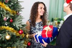 Couples donnant des présents au dîner de Noël Image stock