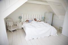 Couples dormant dans la lumière et l'Airy White Bedroom image stock
