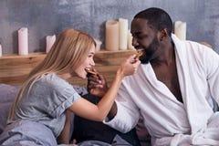 Couples doux s'alimentant avec des biscuits dans le lit Photos stock