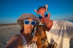 Couples drôles, dans des lunettes de soleil de carnaval, avec un petit chien prenant le Se Image stock