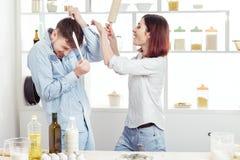 Couples drôles dans l'amour faisant cuire la pâte et ayant l'amusement avec de la farine dans la cuisine Images stock