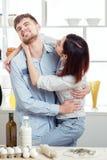 Couples drôles dans l'amour faisant cuire la pâte et ayant l'amusement avec de la farine dans la cuisine Image libre de droits