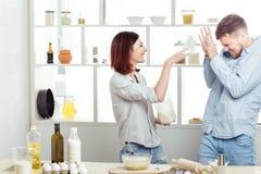 Couples drôles dans l'amour faisant cuire la pâte et ayant l'amusement avec de la farine dans la cuisine Photographie stock libre de droits