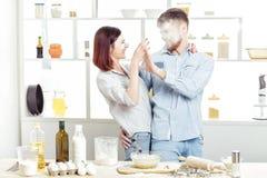 Couples drôles dans l'amour faisant cuire la pâte et ayant l'amusement avec de la farine dans la cuisine Image stock