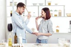 Couples drôles dans l'amour faisant cuire la pâte et ayant l'amusement avec de la farine dans la cuisine Photographie stock