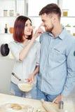 Couples drôles dans l'amour faisant cuire la pâte et ayant l'amusement avec de la farine dans la cuisine Photos stock