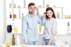 Couples drôles dans l'amour faisant cuire la pâte et ayant l'amusement avec de la farine dans la cuisine Photo libre de droits