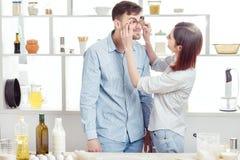 Couples drôles dans l'amour faisant cuire la pâte et ayant l'amusement avec de la farine dans la cuisine Photo stock