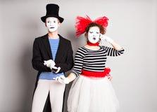 Couples drôles des pantomimes parlant par les téléphones Concept d'April Fools Day Images stock