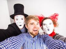 Couples drôles des pantomimes prenant une photo de selfie Photos stock