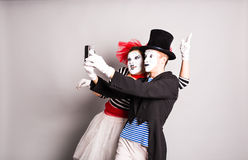 Couples drôles des pantomimes prenant une photo de selfie, April Fools Day Photos stock