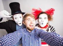 Couples drôles des pantomimes prenant une photo de selfie, concept d'April Fools Day Images libres de droits