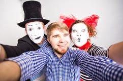Couples drôles des pantomimes prenant une photo de selfie, concept d'April Fools Day Photographie stock libre de droits