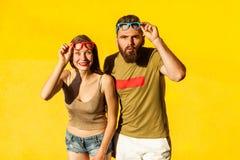 Couples drôles en vêtements de style occasionnel et verres de couleur Photographie stock