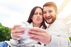 Couples drôles prenant un selfie Photographie stock