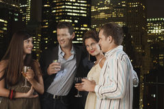 Couples Drinking Against City Skyline At Night. Two young couples drinking together against city skyline at night Stock Image