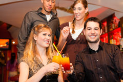 Couples drinking cocktails in bar. Young happy couple drinking cocktails in bar or restaurant, friends are standing in the background Royalty Free Stock Photos