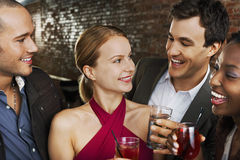 Couples With Drinks At Bar. Two happy multiethnic couples with drinks at the bar Royalty Free Stock Photo
