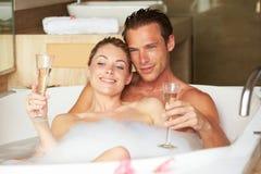 Couples détendant à Bath buvant Champagne Together Images libres de droits
