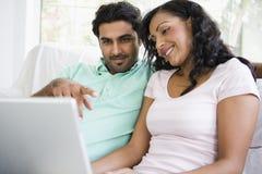 Couples du Moyen-Orient se reposant avec un ordinateur portatif Image stock