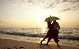 Couples embrassant à la plage dans le coucher du soleil. Images libres de droits