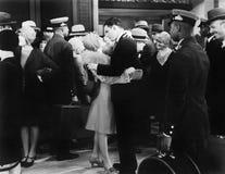 Couples embrassant à une station de train (toutes les personnes représentées ne sont pas plus long vivantes et aucun domaine n'ex Image stock