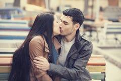 Couples embrassant au banc à l'allée. Image stock