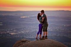 Couples embrassant au coucher du soleil placé sur une montagne Photo stock