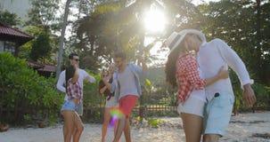 Couples embrassant au-dessus de la danse de groupe de personnes chez les hommes heureux et les femmes de parc tropical de palmier banque de vidéos
