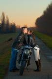 Couples embrassant au-dessus de la moto Image libre de droits