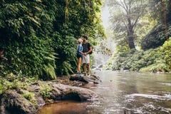 Couples embrassant dans la crique de forêt Photos libres de droits
