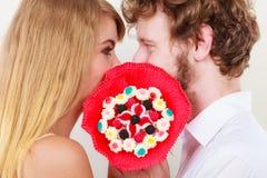 Couples embrassant derrière des fleurs de groupe de sucrerie Amour Photographie stock libre de droits
