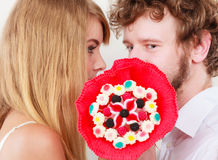 Couples embrassant derrière des fleurs de groupe de sucrerie Amour Images libres de droits
