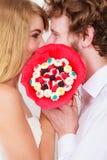 Couples embrassant derrière des fleurs de groupe de sucrerie Amour Photos stock