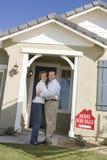 Couples embrassant en Front Of House For Sale Photographie stock libre de droits