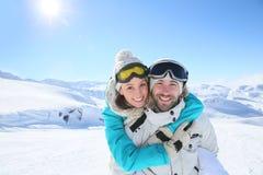 Couples embrassant en montagnes neigeuses Image stock