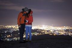 Couples embrassant et lumières de ville de nuit Images libres de droits