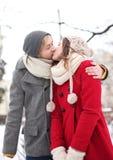 Couples embrassant le jour de l'hiver Image libre de droits